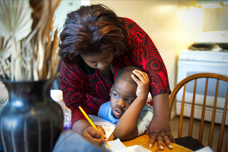 Monique Henderson helps her son, Geramiah, 8, with his homework after school in Camp Springs, MD, Oct. 15, 2013.