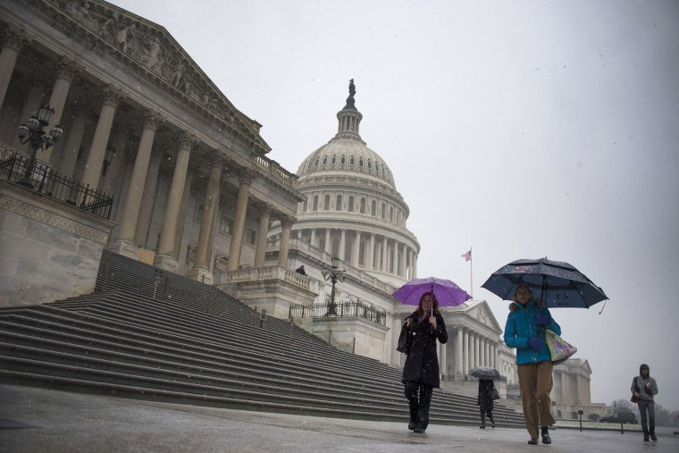 People hold umbrellas as they walk past the US Capitol Building in Washington, DC, Dec. 10, 2013.