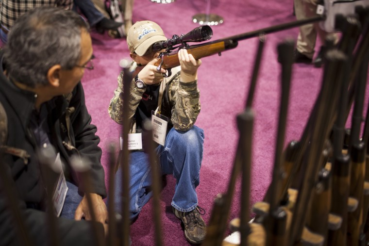 A child checks out a hunting rifle at the Safari Club International Convention in Reno, Nevada, January 29, 2011.