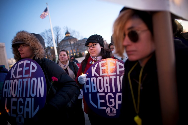 Attendees listen during a candlelight vigil organized by the National Organization for Women in front of the U.S. Supreme Court, Jan. 22, 2013.