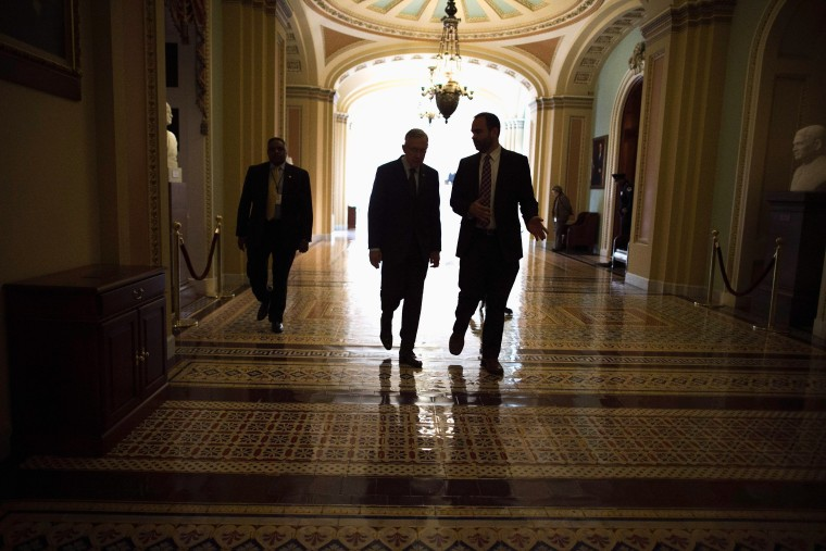 Senate Majority Leader Harry Reid (D-NV) (2nd L) talks with Senior Intelligence and Defense Advisor Tommy Ross (R) while walking through the U.S. Capitol after opening the Senate for the week, January 13, 2014 in Washington, D.C.