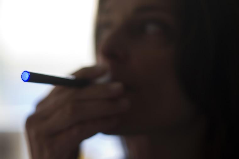 "This Sept. 25, 2013 photo illustration taken in Washington, DC, shows a woman smoking an \""Blu\"" e-cigarette (electronical cigarette)."