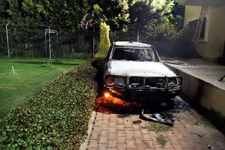 A burnt out vehicle sits smoldering in flames after it was set on fire inside the US consulate compound in Benghazi, Sept. 11, 2012.