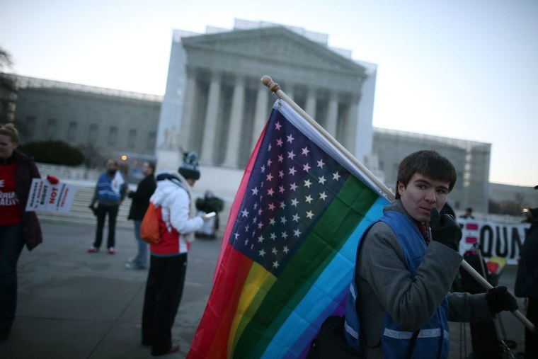 Justin Kenny of Akron Ohio holds a modified Stars and Stripes flag in front of the U.S. Supreme Court, on March 26, 2013 in Washington, D.C.