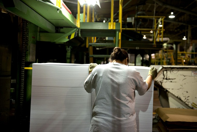 An employee guides a stack of cut paper as it is unloaded from a cutting machine at a paper mill in Rothschild, Wisconsin, U.S., on Wednesday, Oct. 10, 2012.