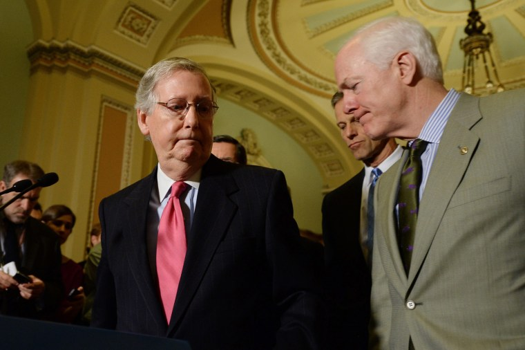 Senate Minority Leader, Republican from Kentucky Mitch McConnell (L), turns away from the podium beside Republican Senator from Texas John Cornyn (R), during a news conference on Capitol Hill in Washington, D.C., January 14, 2014.
