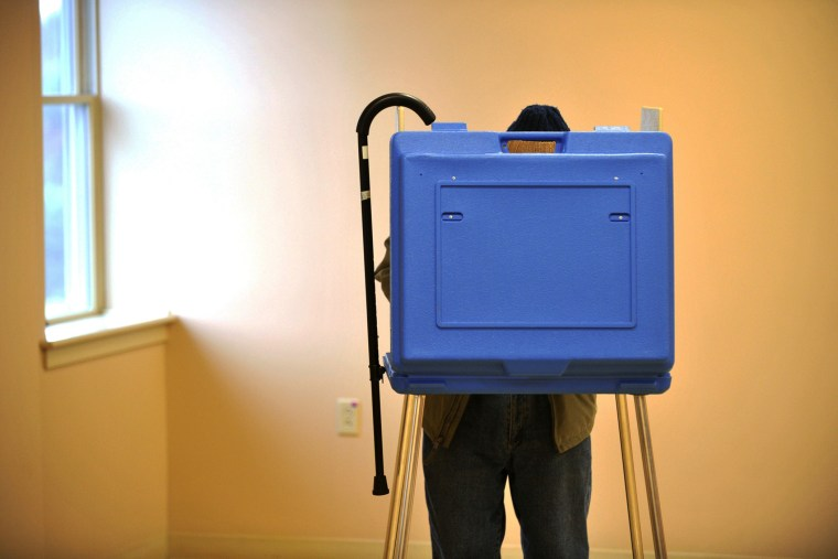 Ninety-one-year-old Dave Silverman hangs his cane on the booth while voting in State College, Pa., Nov. 5, 2013.