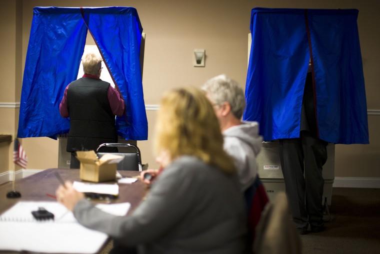 A voter steps into voting booth, Nov. 5, 2013, in Philadelphia, Pa.
