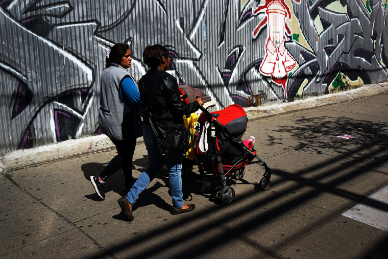 Two women walk down a street in the South Bronx, Sept. 19, 2013.