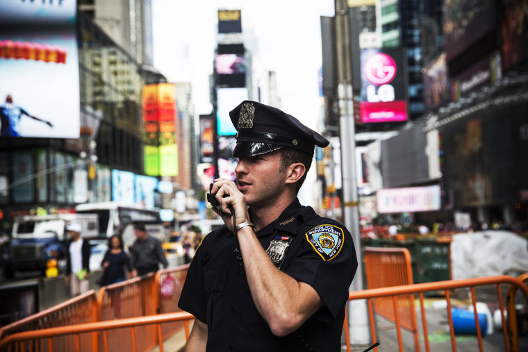 A New York Police Department officer speaks on his radio in Times Square, Sept. 22, 2013.