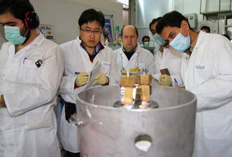 Unidentified International Atomic Energy Agency (IAEA) inspectors (2nd-3rd L) and Iranian technicians disconnect the connections between the twin cascades for 20 percent uranium production at nuclear power plant of Natanz, some 300 kilometres south of Teh