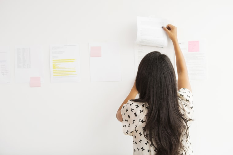 Businesswoman taping up papers on office wall