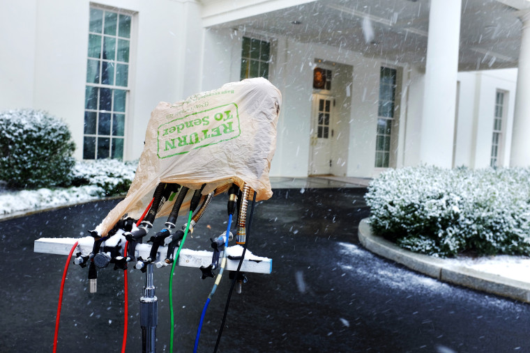 Television microphones are protected by a plastic bag as heavier snow begins to fall outside the West Wing of the White House in Washington, on Jan. 21, 2014.