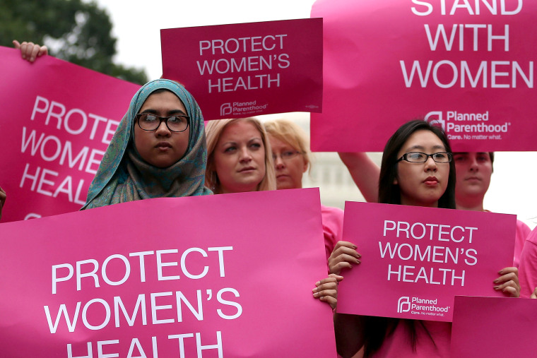 Women hold up signs during a women's pro-choice rally on Capitol Hill, July 11, 2013.