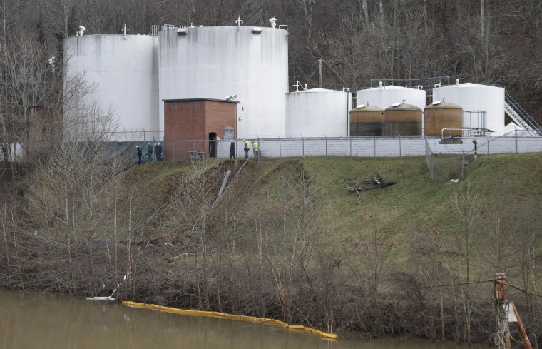 Workers inspect an area outside a retaining wall around storage tanks where a chemical leaked into the Elk River at Freedom Industries storage facility  in Charleston, West Virginia, Monday, Jan. 13, 2014.