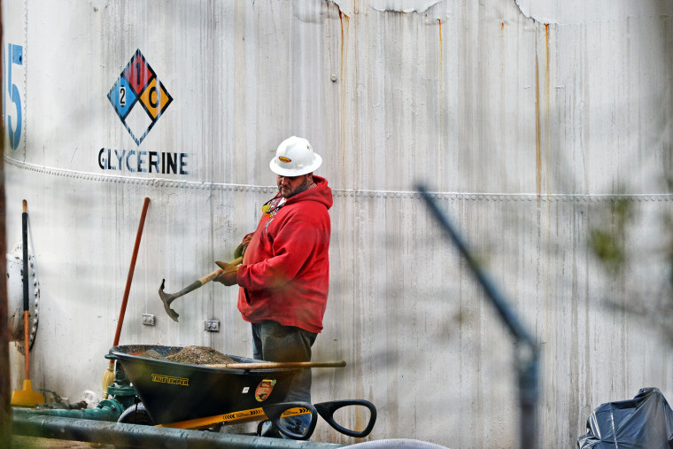 An unidentified worker at Freedom Industries shovels NAPA premium oil absorbent in Charleston, West Virginia, Jan. 10, 2014.