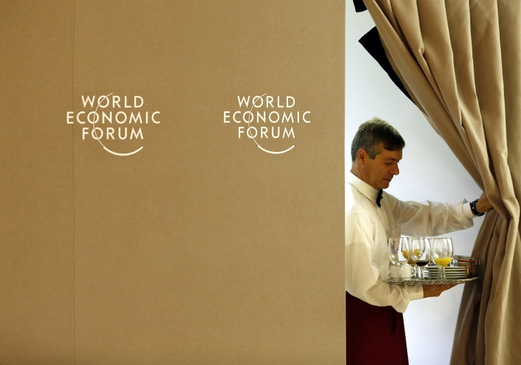 A waiter pulls back a curtain during World Economic Forum in Davos