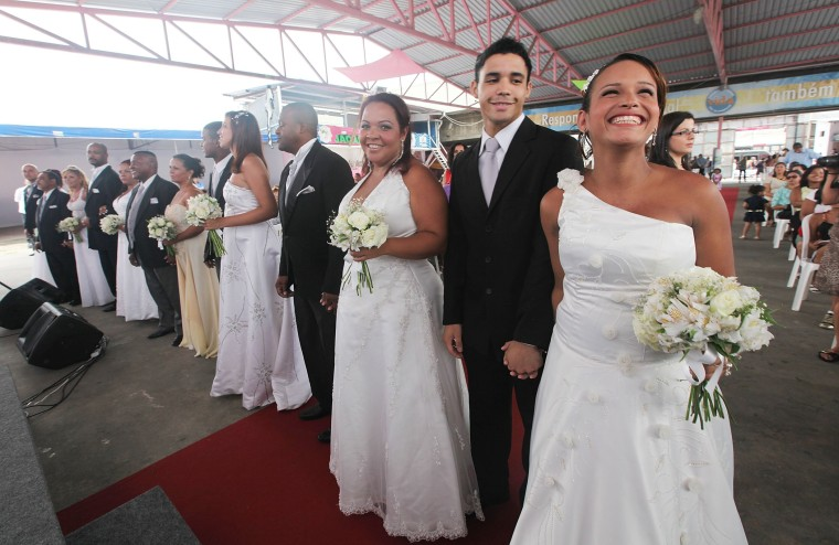 Bride Michelle Nogueira (R) and groom Wellington Costa (2nd R) stand before marrying in a communal marriage ceremony in the Jacarezinho pacified community, or shantytown, on January 17, 2014 in Rio de Janeiro, Brazil.