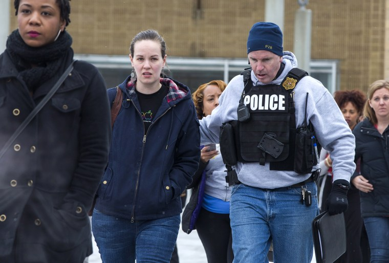 Police escort shoppers and employees out of the Columbia Mall after a shooting left three people dead, Jan. 25, 2014, in Columbia, Md.
