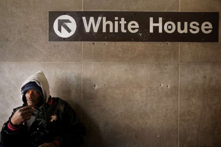 A homeless man steels himself against single-digit temperatures in the McPhearson Square Metro station in Washington, Jan. 7, 2014.