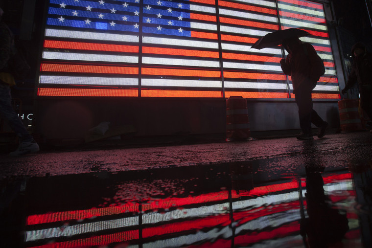 A man walks past a lit US flag with an umbrella at Times Square as it rains in New York, Nov. 26, 2013.