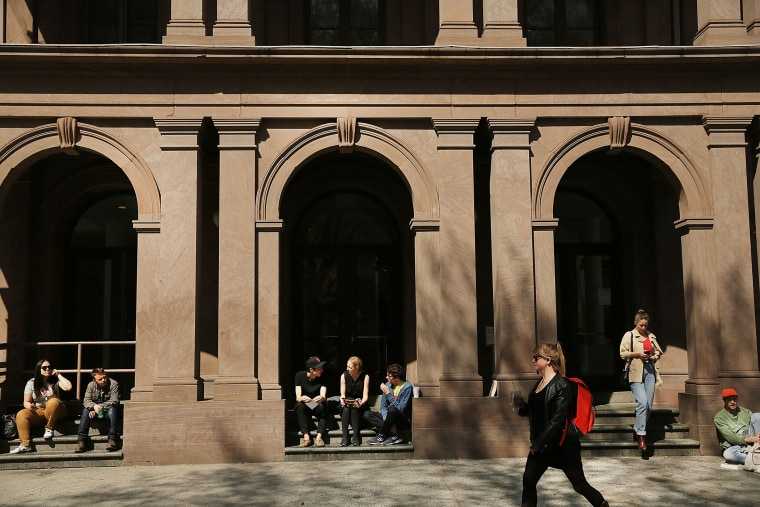 Students sit in front of Cooper Union for the Advancement of Science and Art, on April 24, 2013 in New York City.
