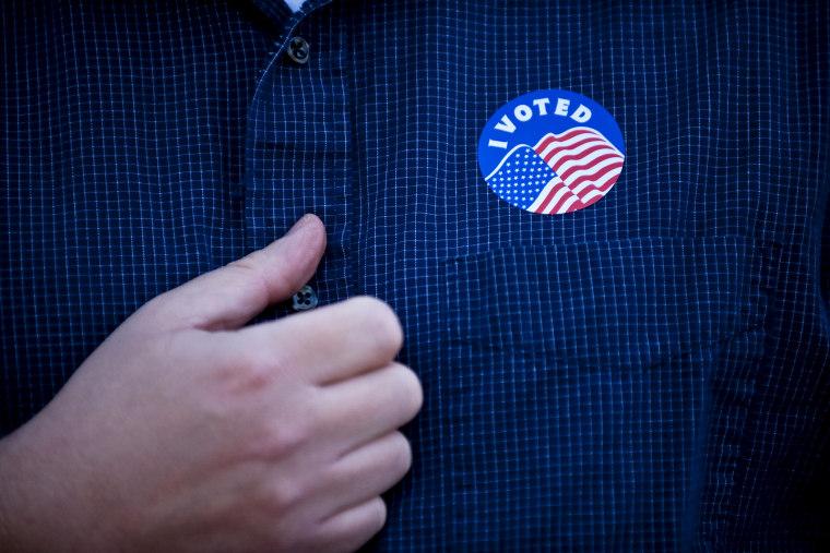 "Rev. Chase Peeples displays his \""I Voted\"" sticker after voting in Kansas City, Missouri, Nov. 6, 2012."