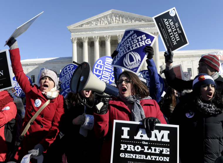Pro-abortion and anti-abortion protestors rally outside the Supreme Court in Washington, Jan. 22, 2014.