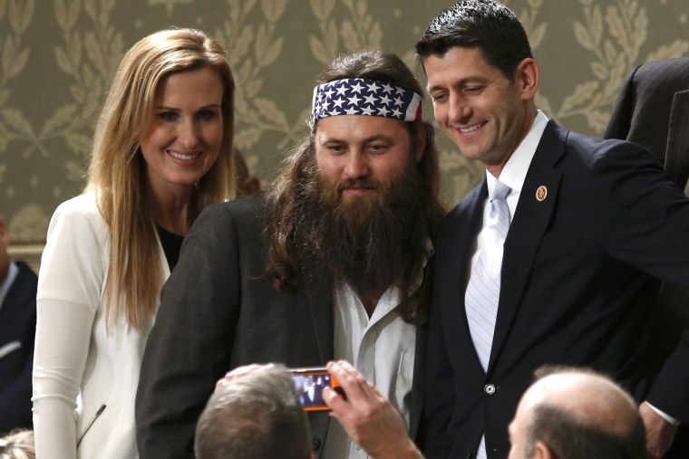 Duck Dynasty television show star Willie Robertson (C) and his wife Korie pose for a picture with U.S. Rep. Paul Ryan (R-WI) before the State of the Union speech at the U.S. Capitol in Washington Jan. 28, 2014.