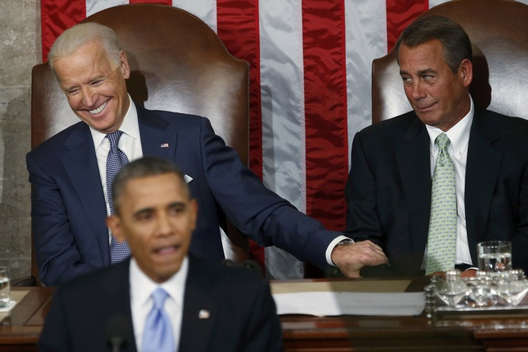 U.S. Vice President Joe Biden (L) grabs the arm of House Speaker John Boehner (R-OH)  as President Barack Obama delivers his State of the Union address in front of the U.S. Congress, on Capitol Hill in Washington, Jan. 28, 2014.