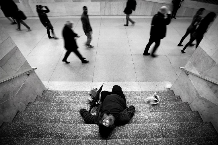 A man sleeps on the stairs of Grand Central Station as commuters pass by on Christmas Eve in New York, Dec. 24, 2013.