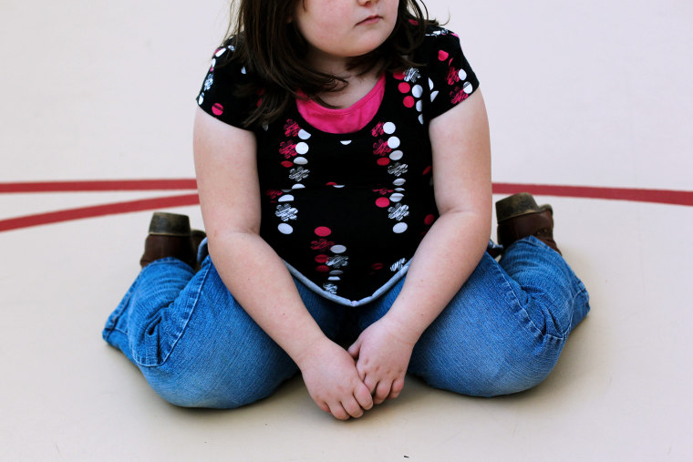 A child sits on the gym floor during the Shapedown program for overweight adolescents in Aurora, Colorado.