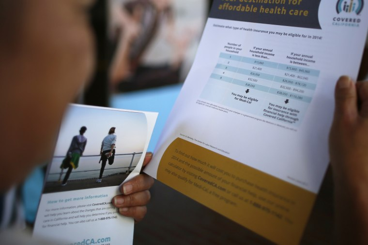 """A potential insurance customer browses leaflets at a """"Covered California"""" event in Los Angeles on Oct. 1, 2013."""