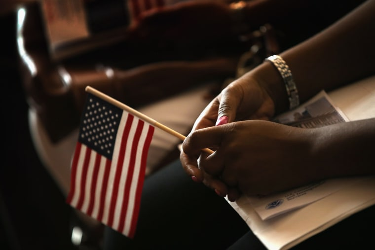 A new U.S. citizen holds an American flag along with her citizenship papers as she participates in a naturalization ceremony at the Chicago Cultural Center on July 3, 2013 in Chicago, Ill.