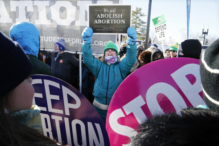 An anti-abortion demonstrator (C) shouts at pro-choice demonstrators in front of the U.S. Supreme Court during the annual March for Life in Washington, January 22, 2014.