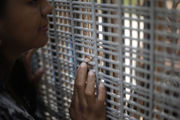 Marta Lopez touches the finger of her daughter Alondra Lopez, 8, as they stand separated by a fence between Tijuana, Mexico, and San Diego on July 14, 2013.