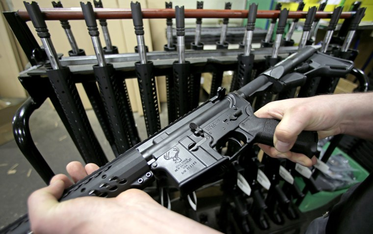 Veetek Witkowski holds a newly assembled AR-15 rifle at the Stag Arms company in New Britain,  Conn, April 10, 2013.