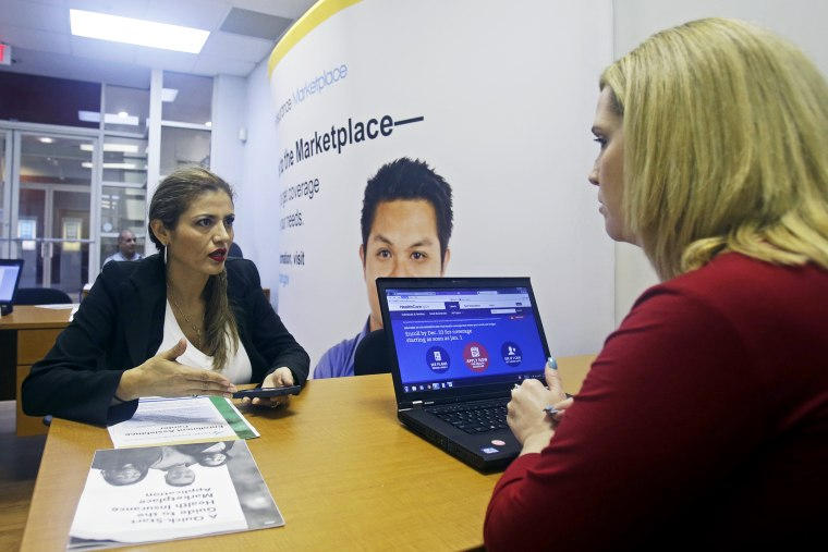 Johanna Diaz, left, talks to Senior Certified Enrollment Specialist Marlene Nesmith, right, at a  Healthcare Marketplace office in Miami, Dec. 20, 2013.