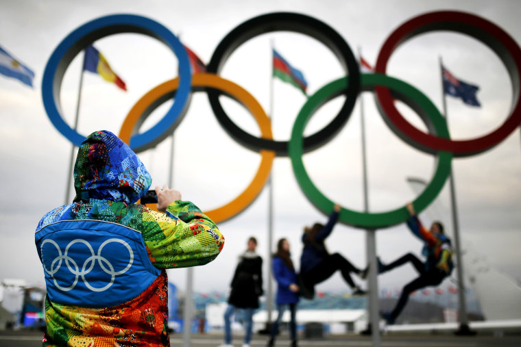 An Olympic volunteer takes pictures of people as they pose under the Olympic rings in Sochi, Jan. 30, 2014.