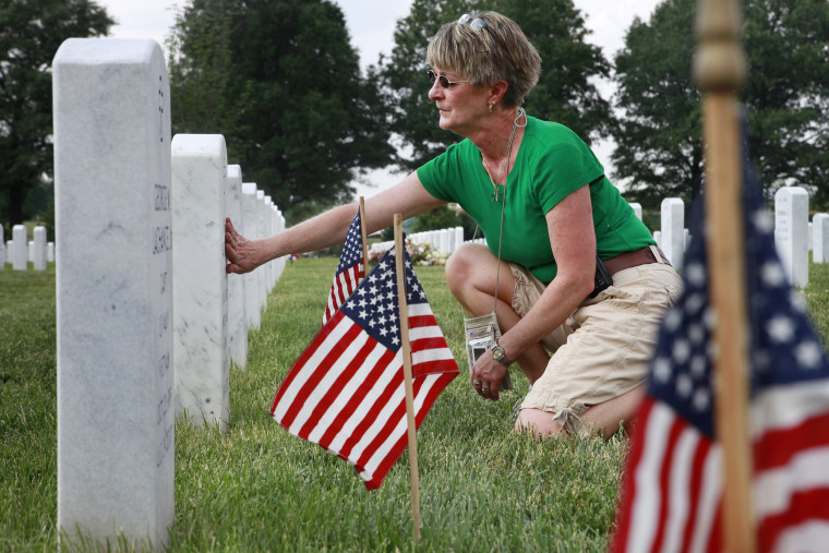 Anita Dixon, of Wichita, Kan., whose son Army Sgt. Evan Parker was killed while serving in Iraq in 2005, touches a grave in Arlington National Cemetery.