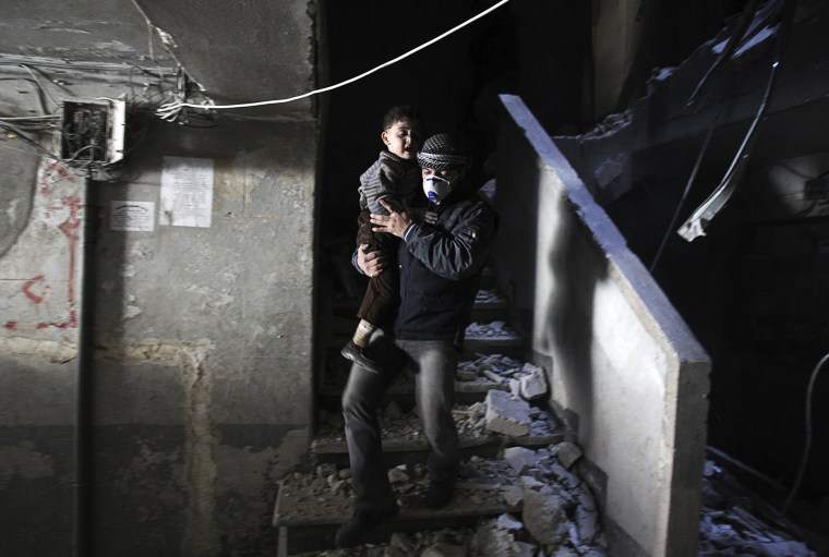 A man wearing a mask holds a child who was rescued at a site hit by what activists said were barrel bombs dropped by government forces, Jan. 31, 2014, in the Al-Ansari neighborhood of Aleppo, Syria.