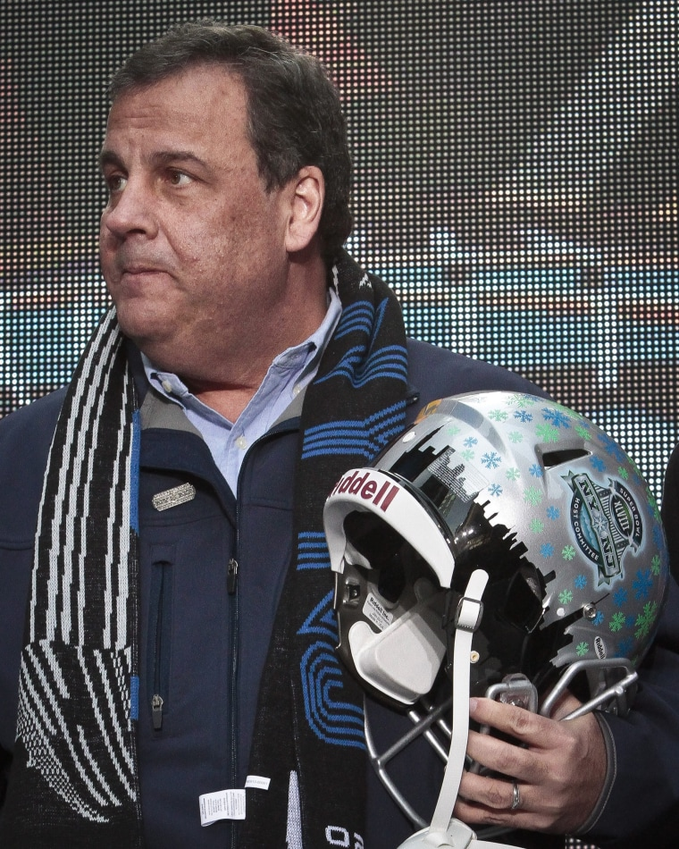 New Jersey Gov. Chris Christie holds a souvenir football helmet as he leaves after a ceremony to pass official hosting duties of next year's Super Bowl to representatives from Arizona, Saturday Feb. 1, 2014 in New York.