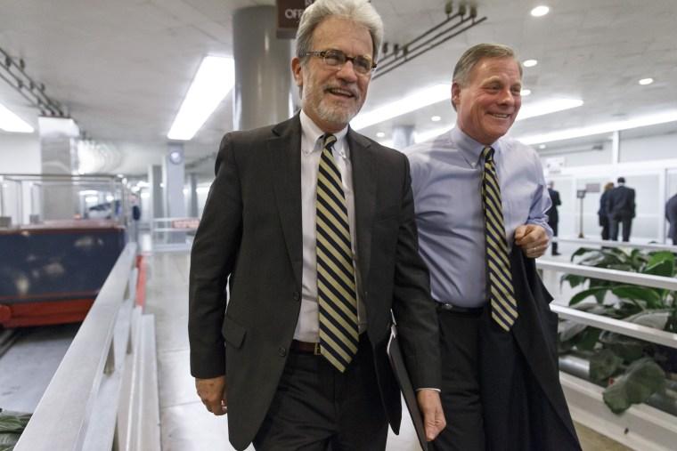 Sen. Tom Coburn, R-Okla., left, walks with Sen. Richard Burr, R-N.C., at the Capitol in Washington, Thursday, Dec. 19, 2013.