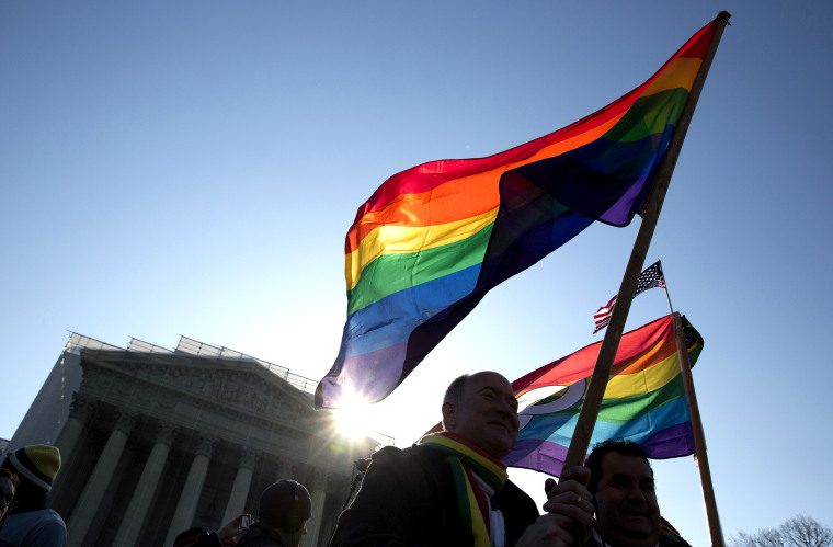 Supporters of gay marriage hold rainbow-colored flags as they rally in front of the Supreme Court in Washington March 27, 2013.