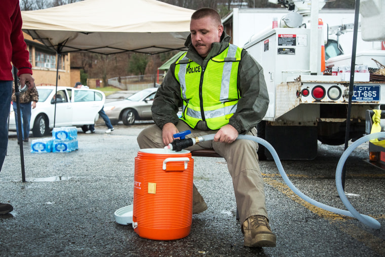 Chief of Police Brian Oxley helps distribute water to local residents, Jan. 11, 2014.