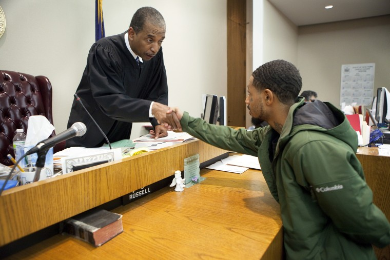 Judge Robert Russell, creator of the Buffalo Veterans Treatment Court, shakes hands with veteran Justin Smith who has succeeded in his court, on Oct. 23, 2012.