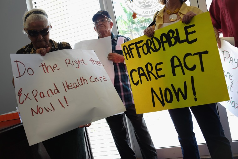 Leonor Cervantes (L) and other protesters gather in the office of Florida State Rep. Manny Diaz as they protest his stance against the expansion of healthcare coverage on September 20, 2013 in Miami, Florida.