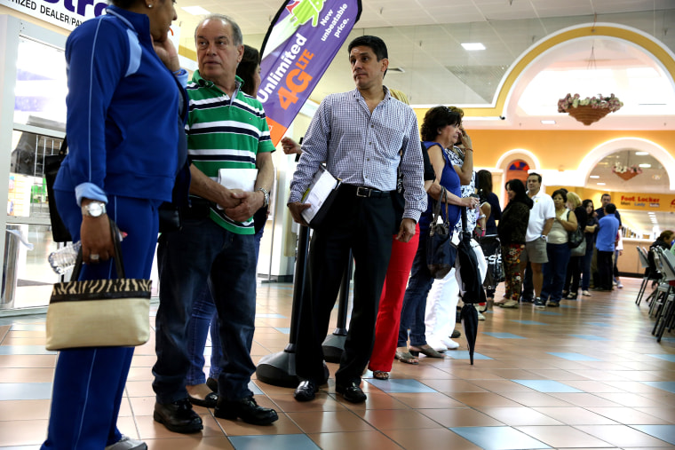 People waiting to speak with an insurance agent as they try to purchase health insurance under the Affordable Care Act at the kiosk setup at the Mall of Americas on Jan. 15, 2014 in Miami, Florida.