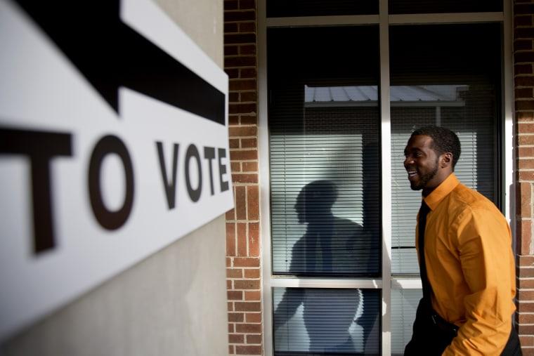 Jovan Steele, of Atlanta, enters a polling station to vote, Tuesday, Nov. 5, 2013.