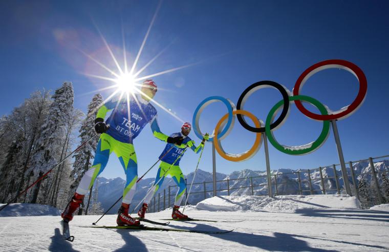 Members of the Slovenian Cross-country ski team ski in front of Olympic rings at Laura Cross-country Ski & Biathlon Center of the 2014 Winter Olympics, Feb. 2, 2014, in Krasnaya Polyana, Russia.